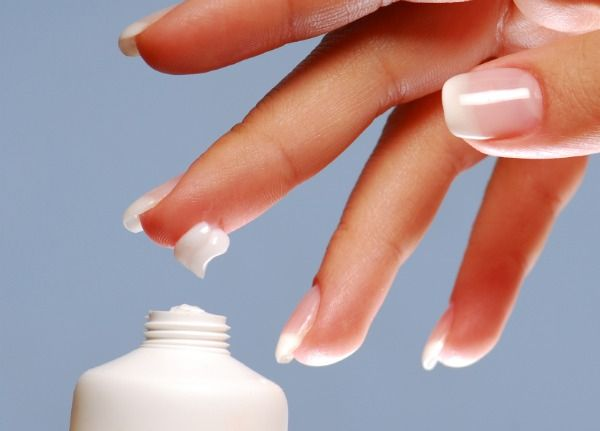 Moisturizer on the end of woman finger.